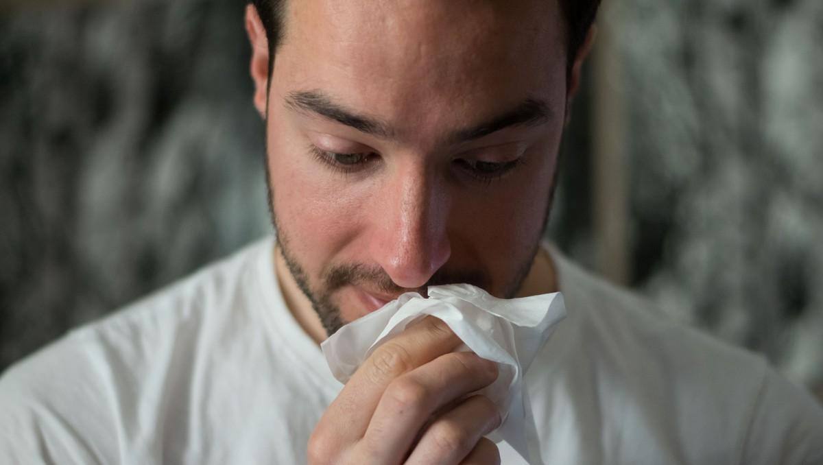Muž trpí na alergie, takže smrká a kýchá.