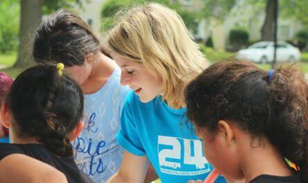 Mladá dívka obklopená dětmi, která se věnuje dobrovolnictví.