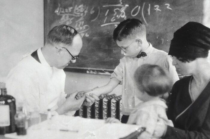 Lékař píchá dětem vitamíny, aby se posílila jejich imunita.